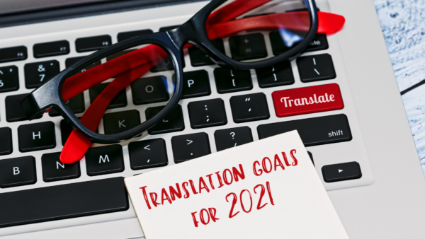 Computer keyboard and a note pad with the text Translation goals for 2021